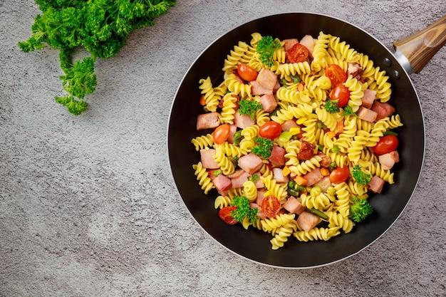 Kleurrijke deegwarenrotini, kerstomaatjes en ham op pan. bovenaanzicht.