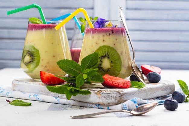Kleurrijke detox gelaagde smoothie met natuurlijke eetbare bloemen, bessen en munt