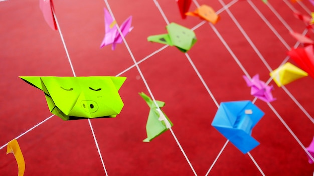 Kleurrijke dierlijke origamidocumenten van jonge geitjes die met witte koorden in speelplaats van school hangen.