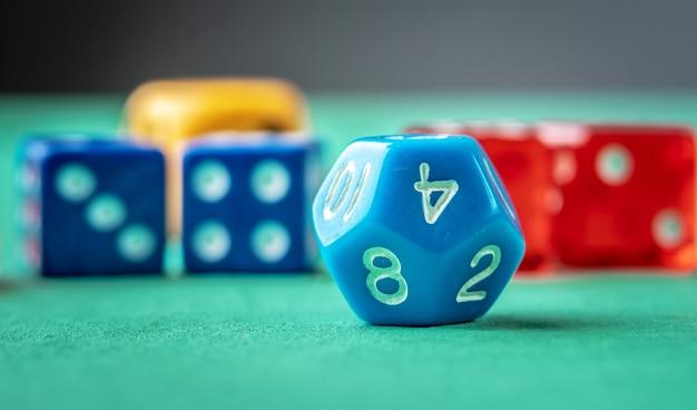 Kleurrijke dobbelstenen op de groene tafel. het concept van een casino en een gelukkige kans om te winnen