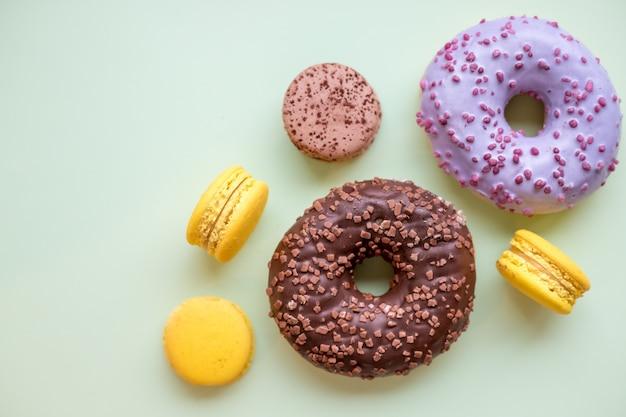 Kleurrijke donuts en bitterkoekjes op houten tafel.