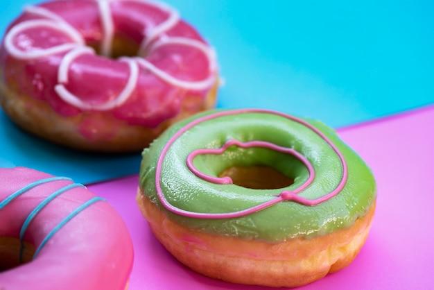 Kleurrijke donuts geplaatst op de vloer blauw met pastel roze kleur