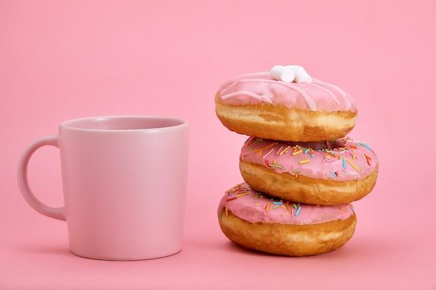 Kleurrijke donuts ontbijtsamenstelling met roze kleurstijlen. spel van kleuren, roze op roze. zoet leven, vanille-ontbijt.
