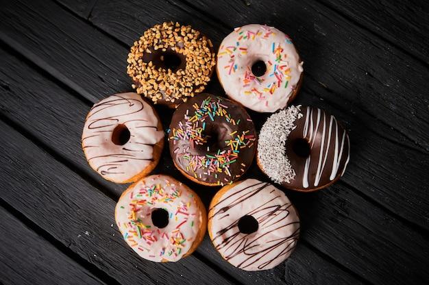 Kleurrijke donuts op stenen tafel. bovenaanzicht met kopie ruimte.