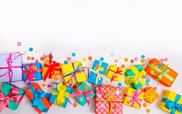 Kleurrijke dozen en confetti op een witte tafel met copyspace, bovenaanzicht