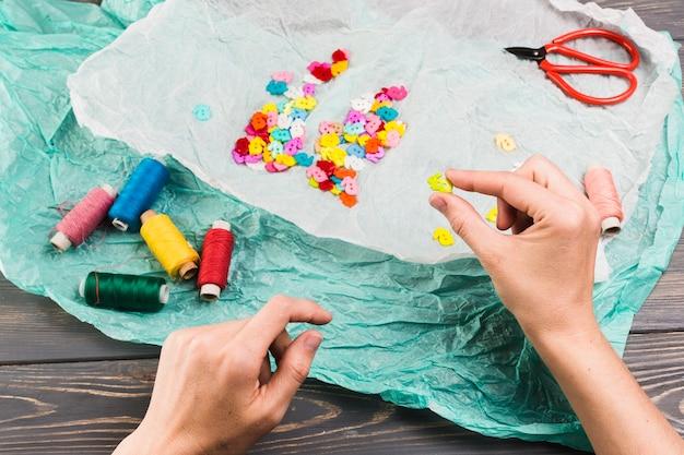 Kleurrijke draadspoelen; knoppen in konijnenvorm en schaar over papier