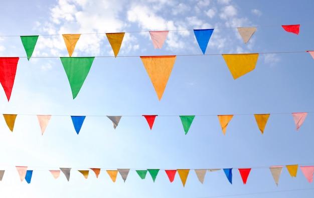 Kleurrijke driehoekige vlaggen opknoping in de lucht buiten.