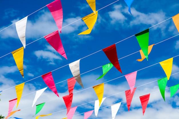 Kleurrijke driehoekige vlaglijn die zich door wind op blauwe hemel witte wolk beweegt