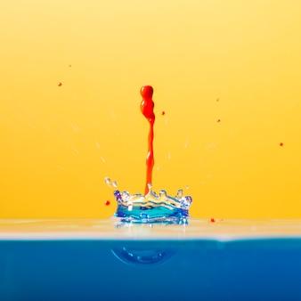 Kleurrijke druppel die in water valt