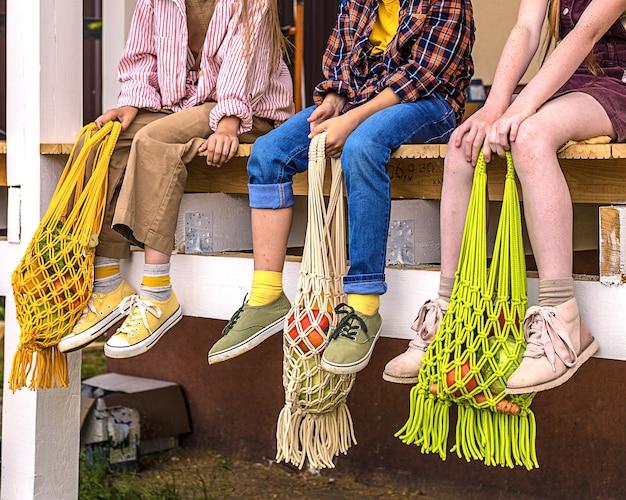 Kleurrijke eco-tassen en kinderpoten