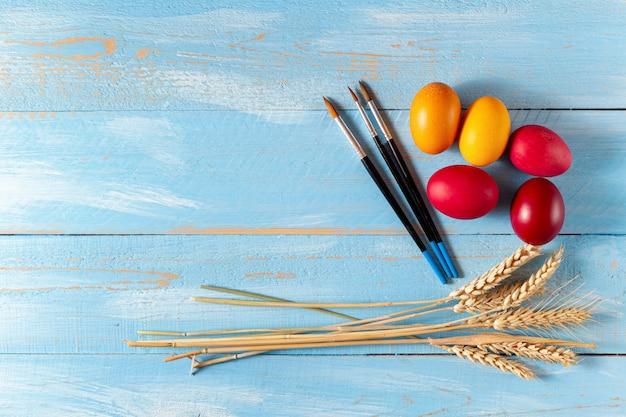 Kleurrijke eieren voor pasen, korenaren en penselen