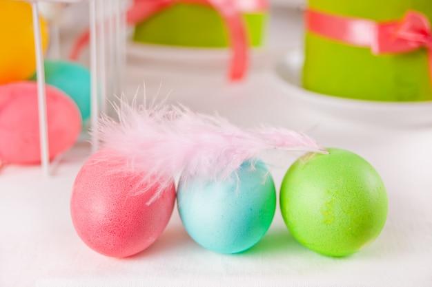 Kleurrijke eieren voor pasen met veer, geschenkdoos en kleine taart