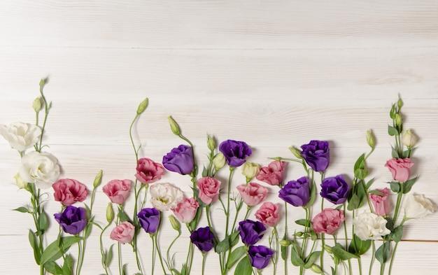 Kleurrijke eustomabloemen op witte houten oppervlakte