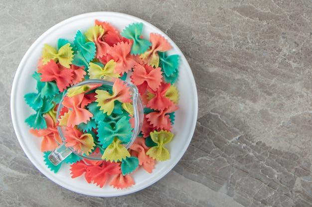 Kleurrijke farfalle pasta in glazen mok