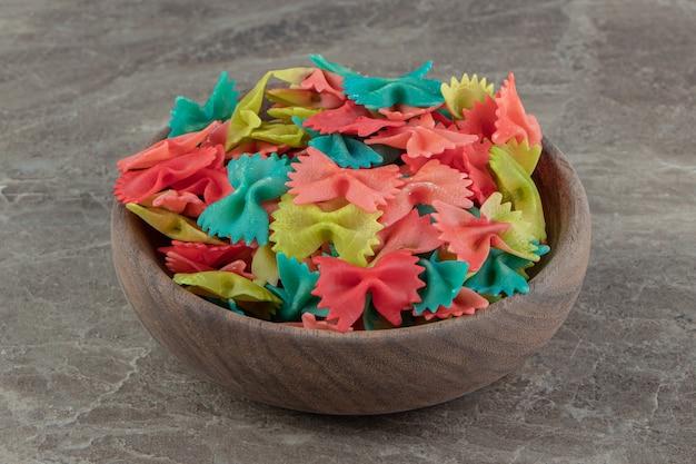 Kleurrijke farfalle pasta in houten kom