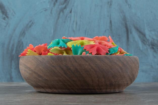 Kleurrijke farfalle pasta in houten kom.