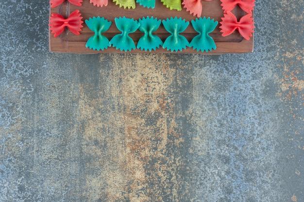 Kleurrijke farfalledeegwaren op het bord, op de marmeren achtergrond.