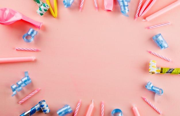 Kleurrijke feestartikelen op een roze tafel.