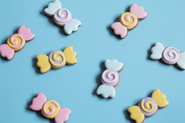 Kleurrijke feestelijke peperkoekkoekjes in de vorm van snoepjes bedekt met glazuur op een blauwe achtergrond.