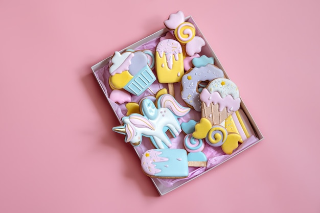 Kleurrijke feestelijke peperkoekkoekjes van verschillende vormen bedekt met glazuur op roze achtergrond.
