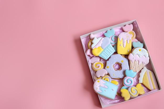 Kleurrijke feestelijke peperkoekkoekjes van verschillende vormen bedekt met glazuur op roze achtergrondkopieerruimte.
