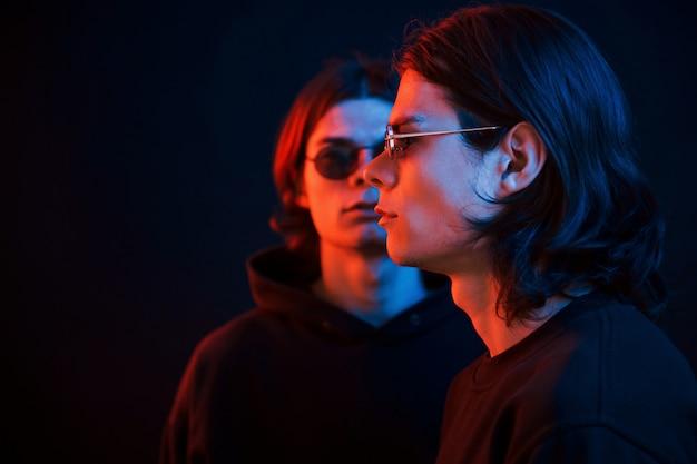 Kleurrijke foto. portret van tweelingbroers. studio opname in donkere studio met neonlicht