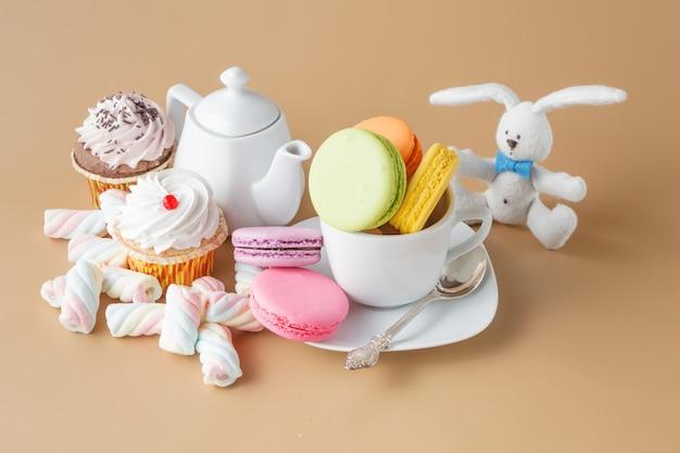 Kleurrijke franse bitterkoekjes en kopje thee op beige achtergrond