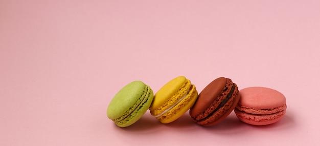 Kleurrijke franse koekjesmakarons op roze achtergrond, exemplaarruimte, horizontale foto