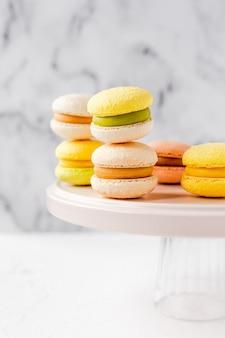 Kleurrijke franse macarons op een roze plaat op marmer