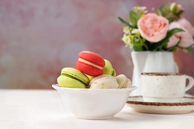 Kleurrijke franse of italiaanse macaronskoekjes op witte kom met exemplaarruimte.