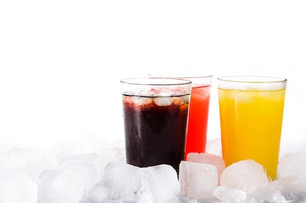 Kleurrijke frisdranken voor de zomer met ijsblokjes op wit