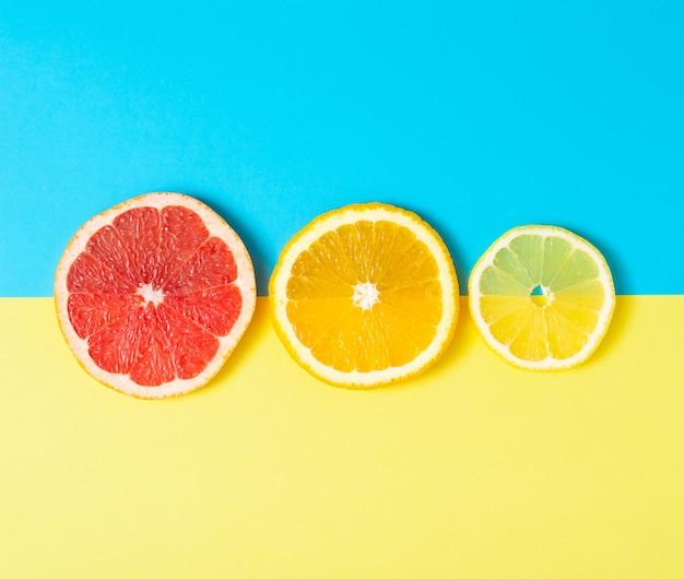 Kleurrijke fruit tropische compositie van verse citrus, citroen, sinaasappel en grapefruit op lichte achtergrond. zomervoedsel creatief plat gelegd.