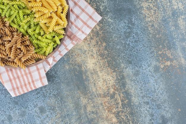 Kleurrijke fusilli pasta's in kom op handdoek, op het marmeren oppervlak.