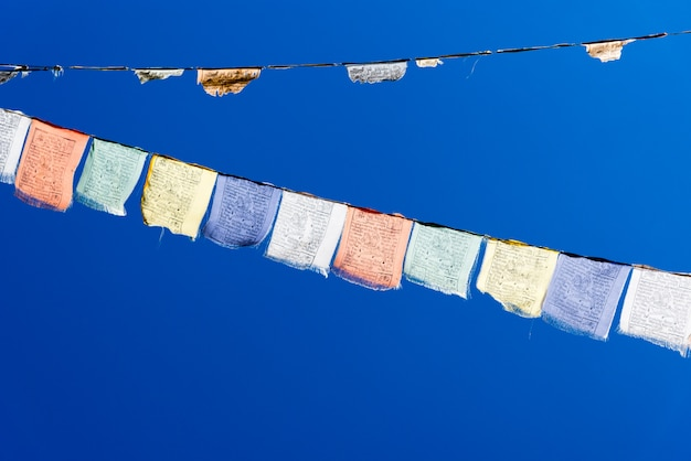 Kleurrijke gebedvlaggen over blauwe hemel.