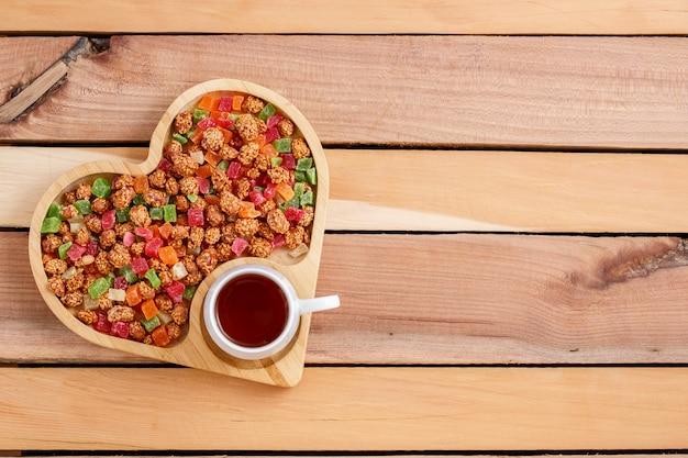 Kleurrijke gedroogde vruchten in een dienblad in de vorm van een hart met thee