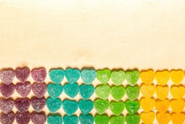 Kleurrijke gelei en snoepjes hart-vormig op houten achtergrond