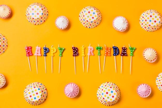 Kleurrijke gelukkige verjaardagskaarsen die met aalaw en stippen document cakevormen worden verfraaid op gele achtergrond