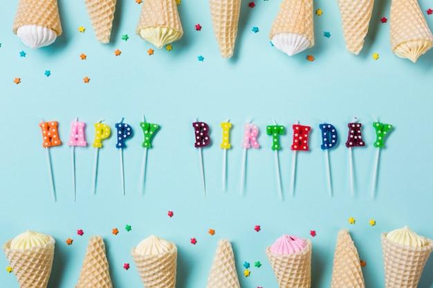 Kleurrijke gelukkige verjaardagskaarsen die met aalaw in de wafelkegel worden verfraaid op blauwe achtergrond