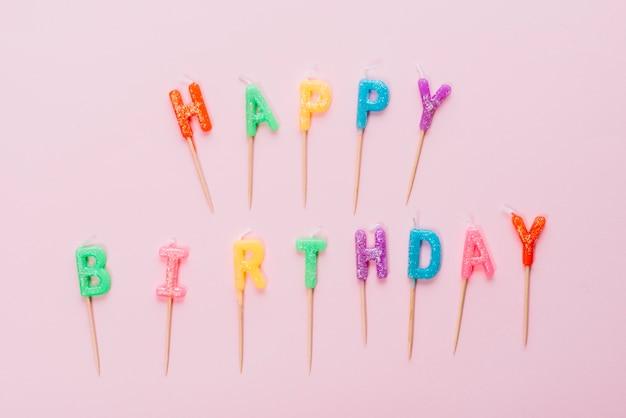 Kleurrijke gelukkige verjaardagskaarsen met stok op roze achtergrond