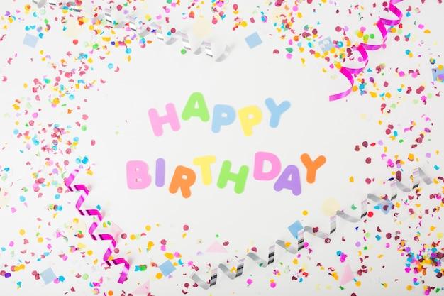 Kleurrijke gelukkige verjaardagstekst met confettien en krullende wimpels op witte achtergrond