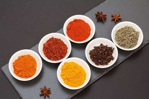 Kleurrijke gemalen specerijen, droge kruidnagel en kruiden in porseleinen kommen op zwarte stenen snijplank. bovenaanzicht.