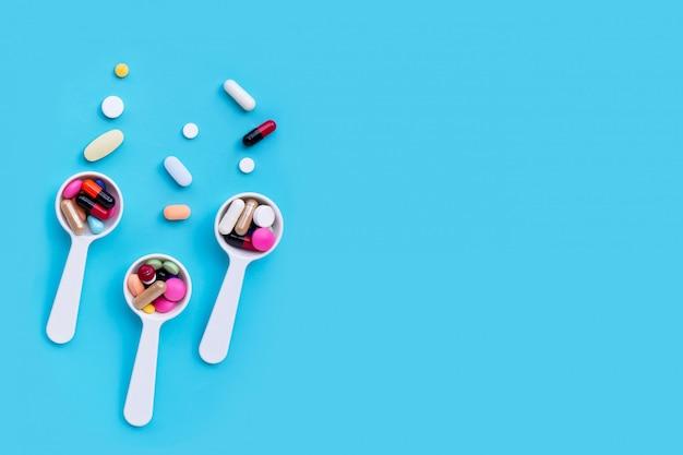 Kleurrijke geneeskundepillen, tabletten en capsules op blauw