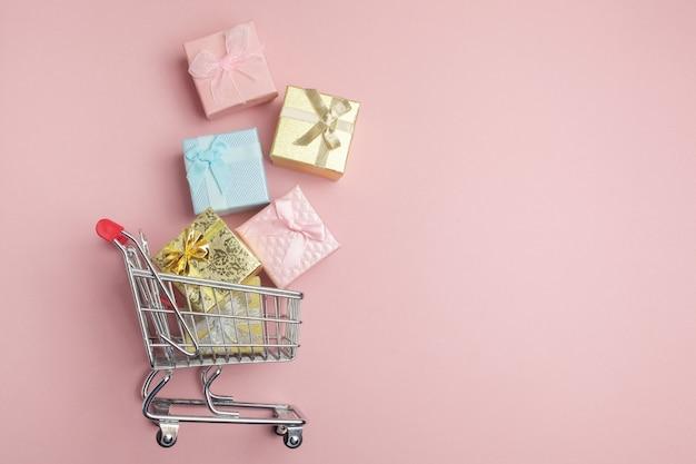 Kleurrijke geschenkdoos, supermarkt winkelwagentje op roze achtergrond