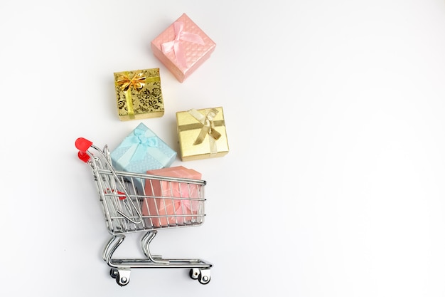 Kleurrijke geschenkdoos, supermarkt winkelwagentje op witte houten achtergrond