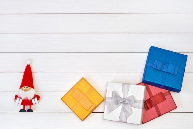 Kleurrijke geschenkdozen en santa op witte houten achtergrond. bovenaanzicht,