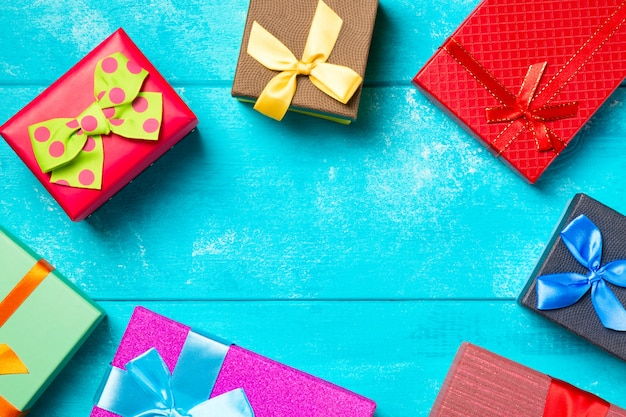 Kleurrijke geschenkdozen met linten op mooie blauwe houten achtergrond