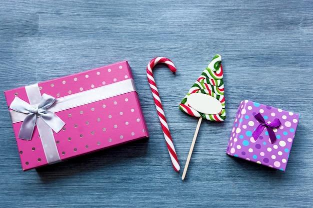 Kleurrijke geschenkdozen van roze en paarse kleur op een houten tafel.