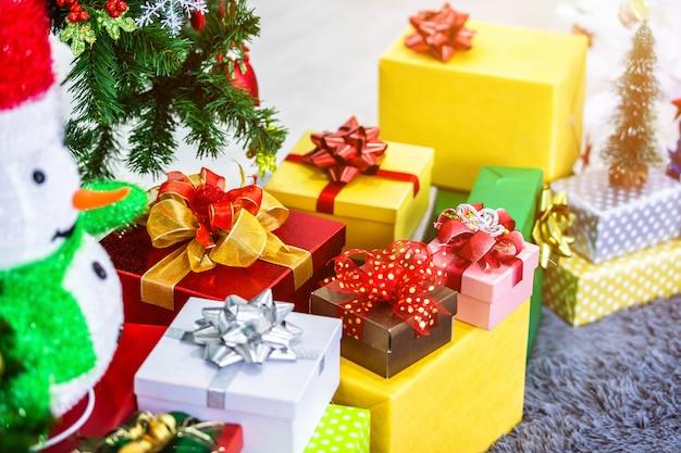 Kleurrijke geschenken en sneeuwpop onder de kerstboom