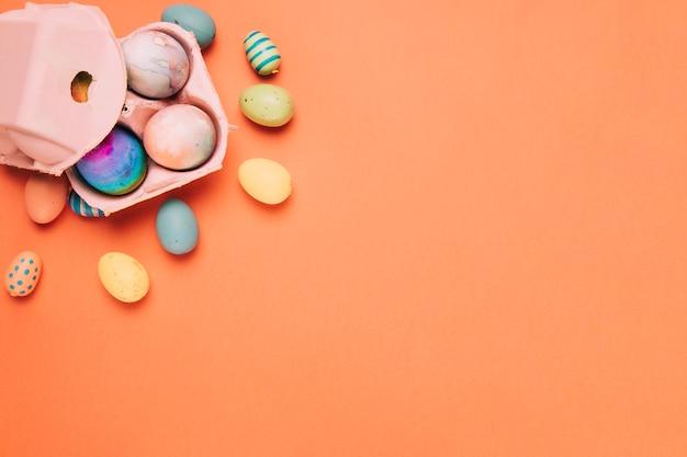 Kleurrijke geschilderde paaseieren en kartondoos op een oranje achtergrond