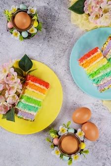 Kleurrijke gesneden cake met bruine eieren voor pasen op houten achtergrond.